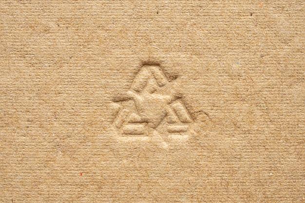 Recycling-zeichen auf braunem papppapier-texturhintergrund
