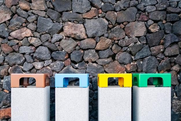 Recyclingbehälter aus verschiedenen materialien auf einem steinanker