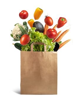 Recyclingfähige papiertüte mit explosion von fliegendem gemüse, konzept für gesunde lebensmittel und ökologisches recycling