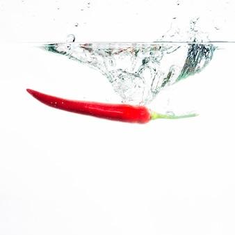 Red chili fällt tief unter wasser mit einem großen spritzer