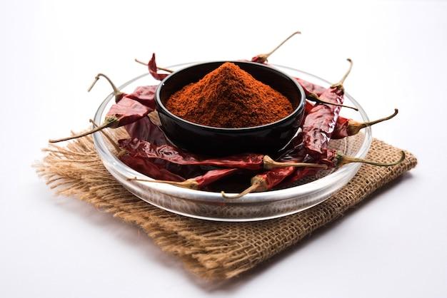 Red chilly oder mirchi mit pulver in einer schüssel über stimmungsvollem hintergrund, selektiver fokus