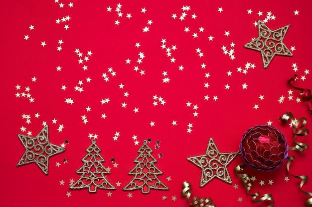 Red christmas hintergrund. weihnachtsverzierungen und goldene sterne auf hellem rotem hintergrund.