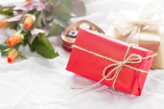 Red geschenk mit blumen neben
