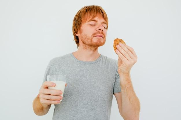 Red-haired mann mit glas milch riechen cookie