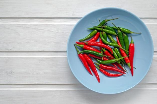 Red hot chili peppers auf modernem hintergrund oder weißem tisch, auf einem runden blauen teller. viele rote und grüne scharfe chilischoten. kopieren sie platz für ihren text. flache lage, draufsicht.