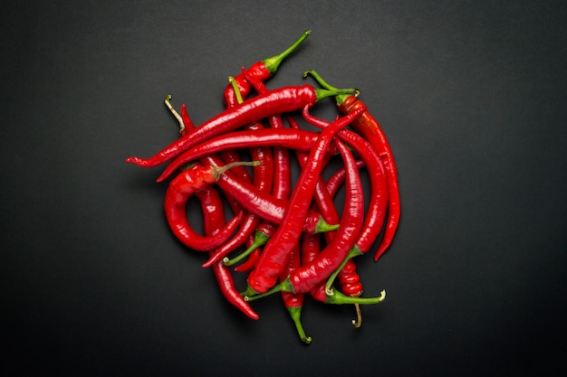 Red hot chili pfeffer in einer kreisform gegen eine schwarze oberfläche ausgekleidet. flache lage, draufsicht