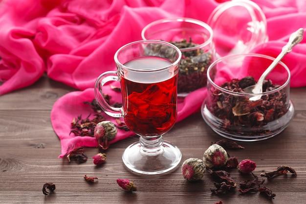 Red hot hibiscus tee in einem glasbecher auf einem holztisch und trockenem tee vanillepudding