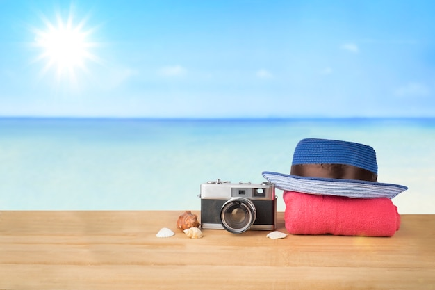 Red rosa turm, blauen hut, alte vintage-kamera und muscheln über holztisch auf sonnenschein blauen himmel und ozean hintergrund