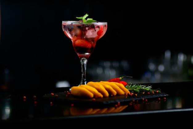 Red strawberry cocktail drink mit gewürzen, pfeffer und basilikum auf einem tisch mit apettizers - selektiver fokus