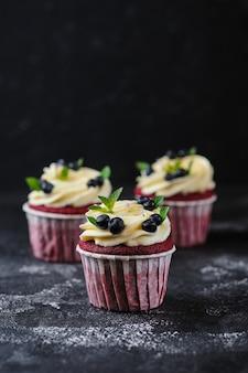 Red velvet cupcakes mit frischkäsecreme. dessert garniert mit frischen blaubeeren und minze.