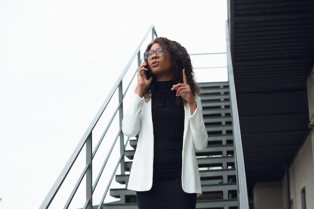 Reden. afroamerikanische geschäftsfrau in bürokleidung lächelnd, sieht selbstbewusst und ernst aus, beschäftigt. konzept für finanzen, wirtschaft, gleichstellung und menschenrechte. schönes junges modell, erfolgreich.