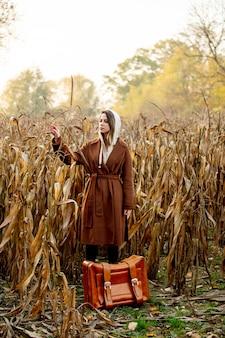 Reden sie frau im mantel mit koffer auf maisfeld in der herbstzeitjahreszeit an