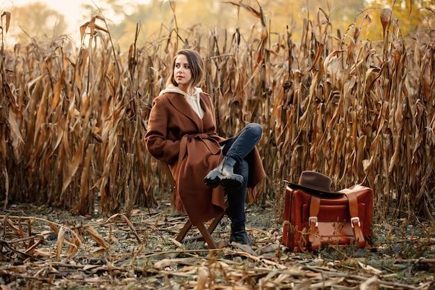 Reden sie frau mit dem koffer an, der auf stuhl auf maisfeld in der herbstzeitjahreszeit sitzt