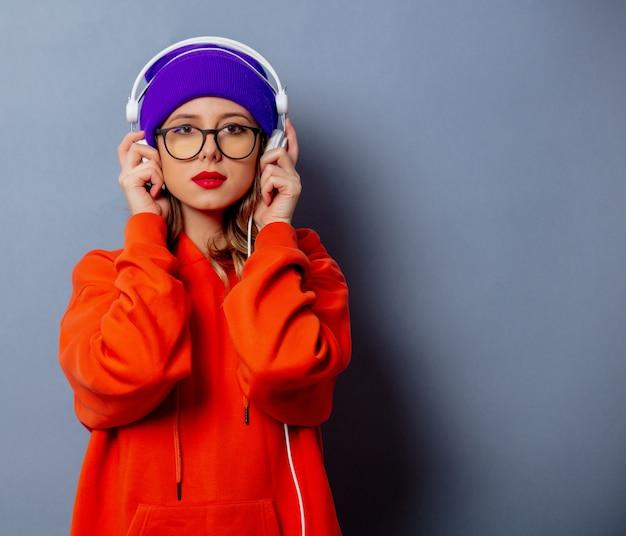 Reden sie mädchen im orange hoodie und im purpurroten hut mit kopfhörern auf grauer wand an