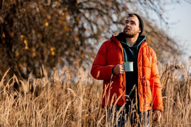 Reden sie mann in der daunenjacke mit tasse kaffee am ländlichen herbst im freien an