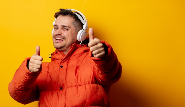Reden sie mann in der jacke 90s mit kopfhörern auf gelber wand an