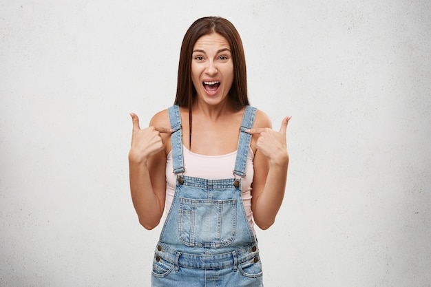 Redest du über mich? innenaufnahme einer emotionalen wütenden empörten teenagerin, die laut schreit und mit den fingern auf sich selbst zeigt, während sie sich mit ihrem freund streitet und gereizt und genervt aussieht