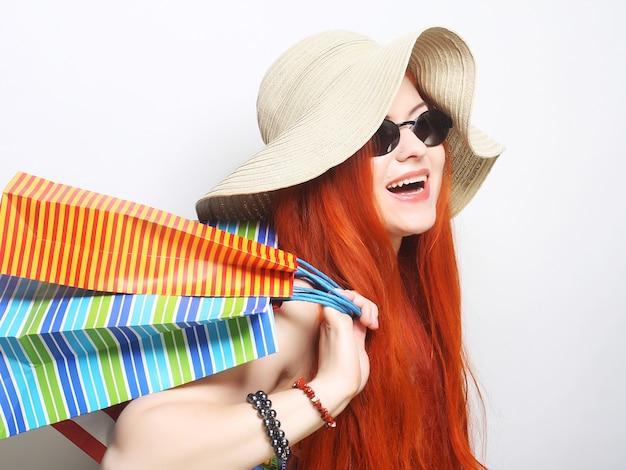 Redhair shopping frau mit sonnenbrille und hut