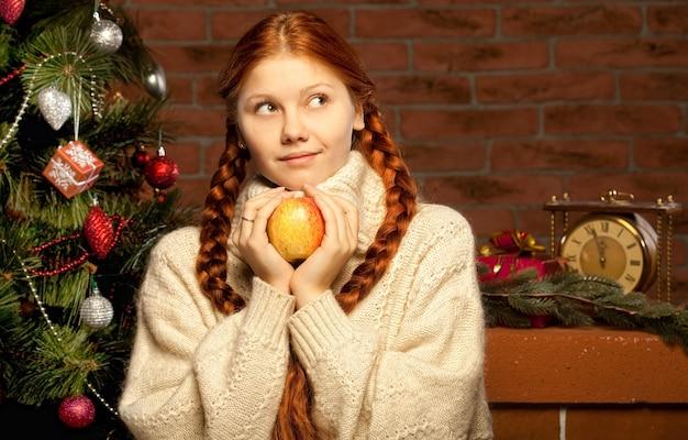 Redhair weihnachtsfrau mit apfel. wohnraum.