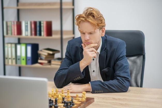 Redhaired ernsthafter mann, der über schachbewegung vor schachbrett und offenem laptop nachdenkt