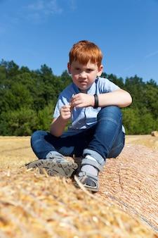 Redhaired junge sitzt auf einem goldenen strohstapel