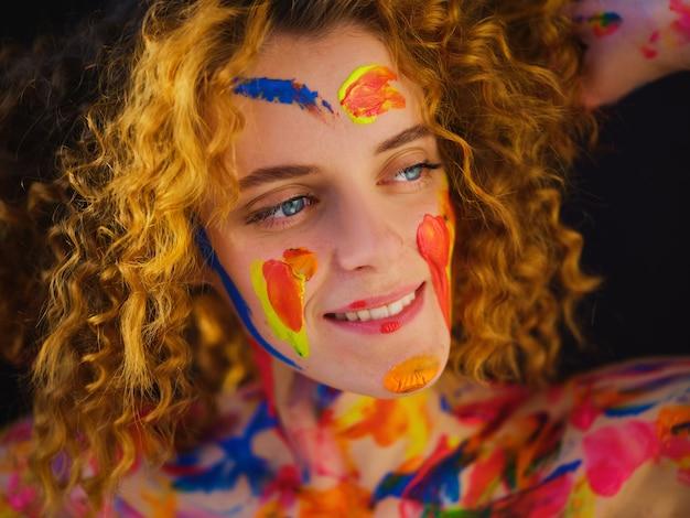 Redhead girl mit bunten farben auf gesicht und körper