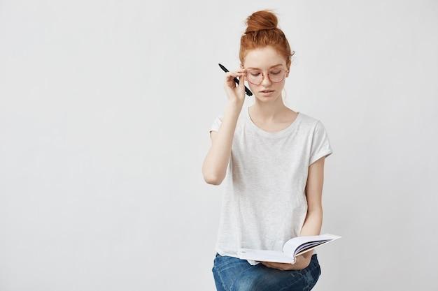 Redhead studentin, die brille korrigiert, die notizbuch hält.
