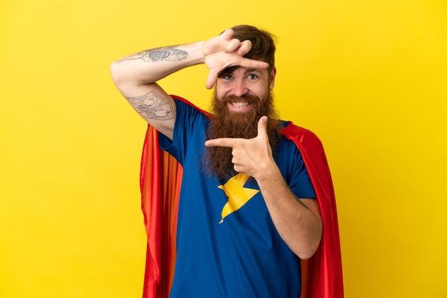 Redhead super hero mann auf gelbem hintergrund fokussierung gesicht isoliert. rahmensymbol
