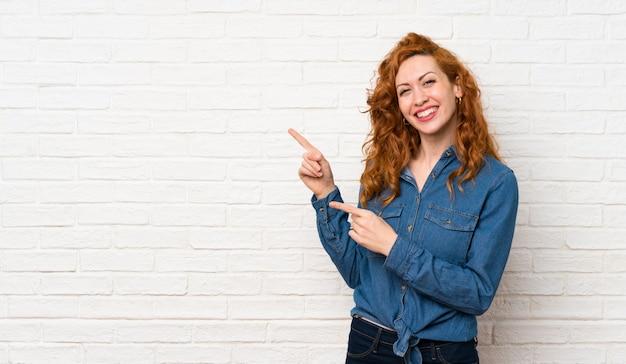 Redheadfrau über weißer backsteinmauer finger auf die seite zeigend