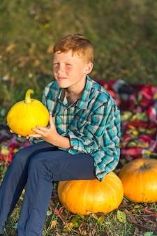 Redheadjunge, der auf einem gelben kürbis sitzt