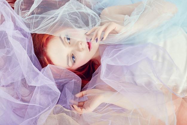 Redheadmädchen in einem hellen luft farbigen kleid liegt auf dem fußboden, eine portraitnahaufnahme