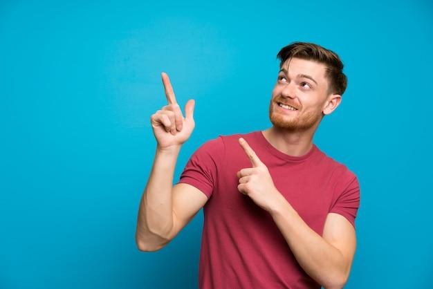 Redheadmann auf getrennter blauer wand zeigend mit dem zeigefinger eine großartige idee