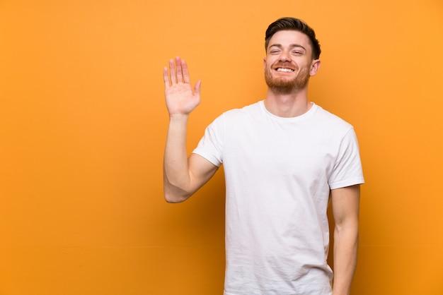 Redheadmann, der mit der hand mit glücklichem ausdruck begrüßt
