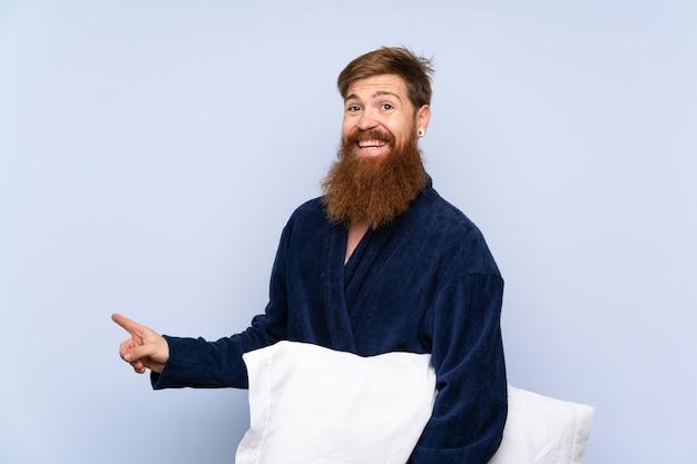 Redheadmann in den pyjamas über getrennter wand überraschte und finger auf die seite zeigend