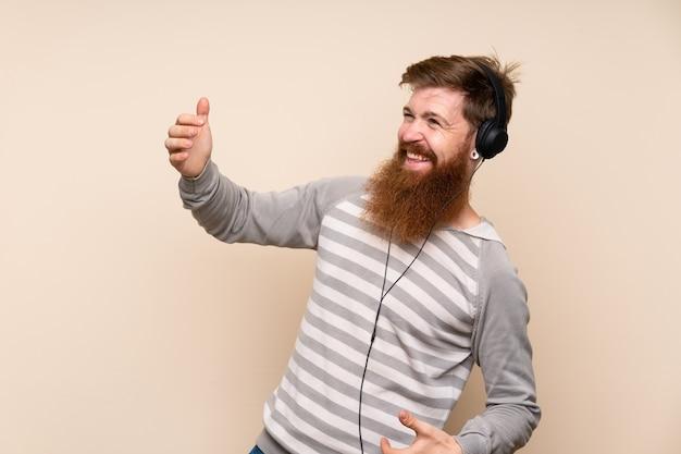 Redheadmann mit dem langen bart, der das mobile mit kopfhörern und dem tanzen verwendet
