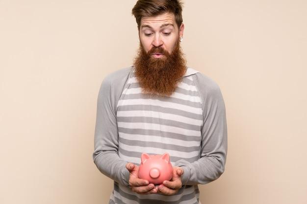 Redheadmann mit dem langen bart, der ein großes piggybank anhält