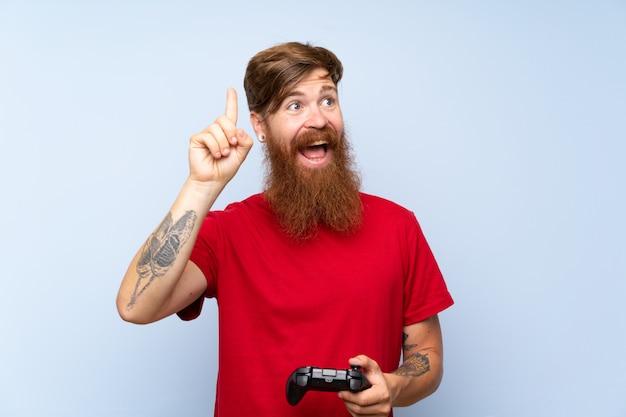 Redheadmann mit dem langen bart, der mit einem videospielprüfer spielt, der beabsichtigt, die lösung beim anheben eines fingers zu verwirklichen