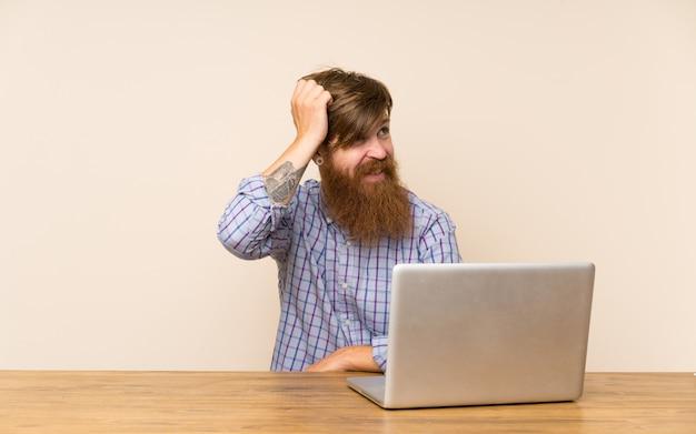 Redheadmann mit langem bart in einer tabelle mit einem laptop, der zweifel hat und mit verwirren gesichtsausdruck