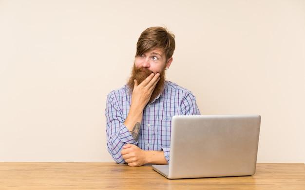 Redheadmann mit langem bart in einer tabelle mit einem laptop eine idee denkend