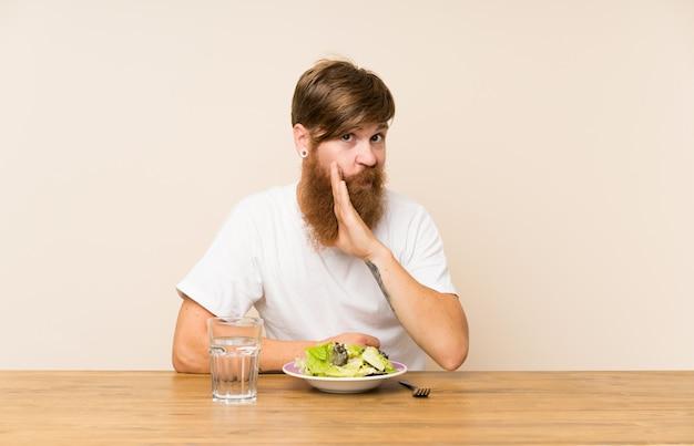 Redheadmann mit langem bart und mit dem salat, der etwas flüstert
