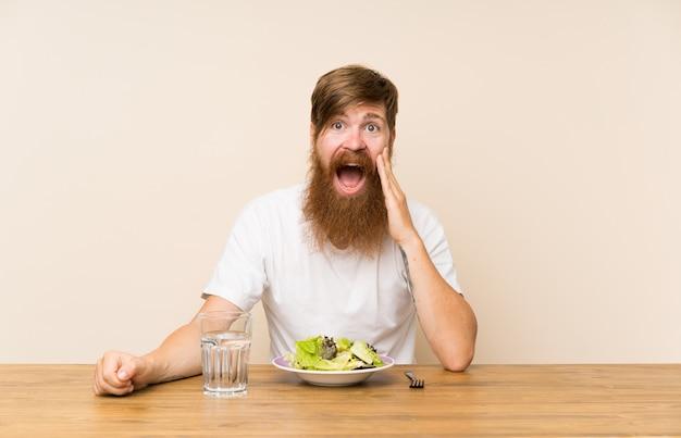 Redheadmann mit langem bart und mit salat mit überraschung und entsetztem gesichtsausdruck