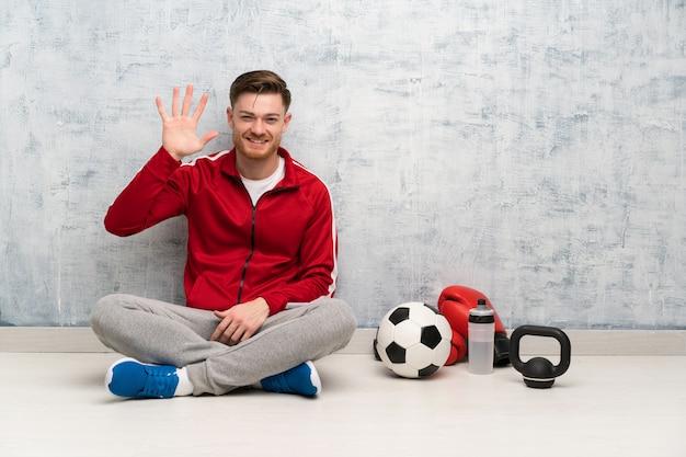 Redheadsportmann, der fünf mit den fingern zählt