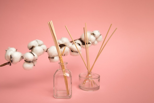 Reed diffusoren auf rosa hintergrund. lufterfrischer mit baumwollblütenbällen riechen sanft nach hause. aromatische sticks mit blumigem geruch. gewerbliche wohnung lag, verspottete vorderansicht. aromatherapie-duft