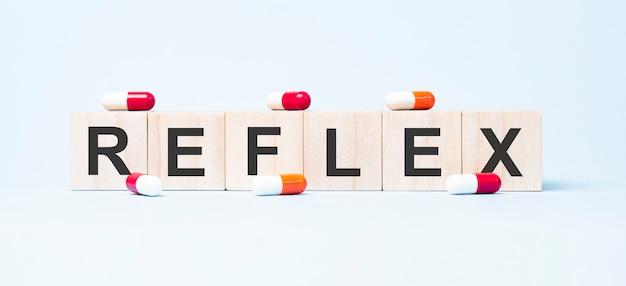 Reflex wort gemacht auf hölzernen würfelblöcken und blume in einem topf auf hintergrund. gesundheits- und medizinkonzept.