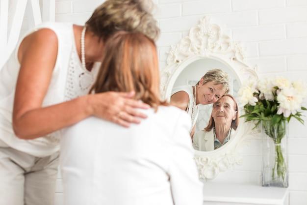 Reflexion der älteren mutter und der reifen tochter auf spiegel zu hause