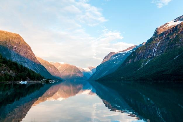 Reflexion der felsigen berge und des himmels auf schönem see