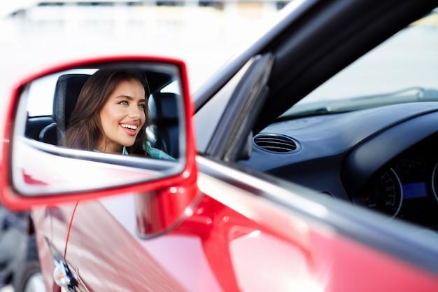 Reflexion der frau, die im roten auto sitzt, glücklicher fahrer. frau, die rückspiegel betrachtet. porträt der glücklichen frau im auto
