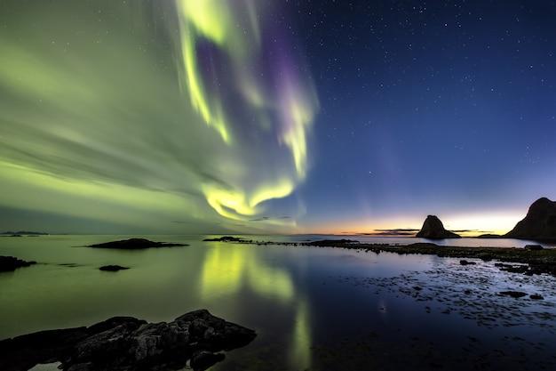 Reflexion der schönen nordlichter im meer, umgeben von hügeln in norwegen