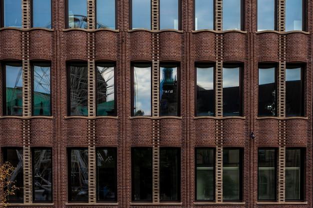 Reflexion der stadt im glas eines historischen industriegebäudes.