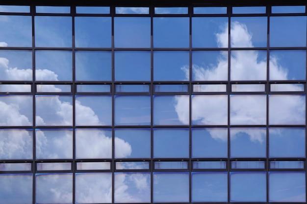 Reflexion des blauen himmels des sommers und der weißen wolken auf dem spiegel des modernen gebäudes